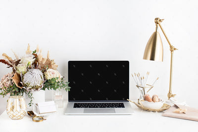 warm neutral desktop image with a neutral floral display, gold lamp, and laptop