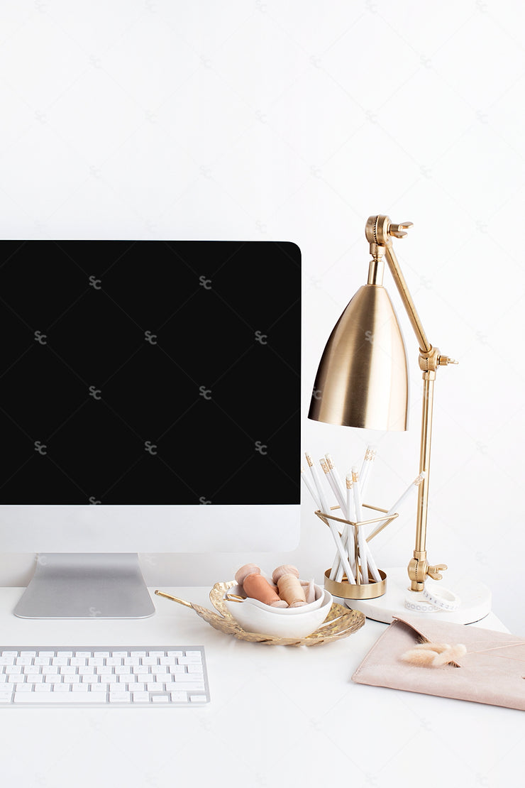 warm neutral desktop computer image with desktop display and a gold lamp