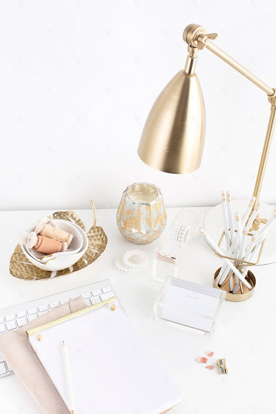 warm neutral desktop with blank paper, gold accents, and a gold desk lamp