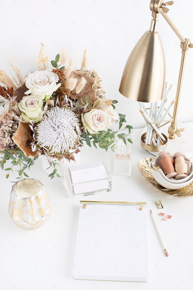 warm neutral desktop with neutral florals, blank paper, gold accents, and a gold desk lamp