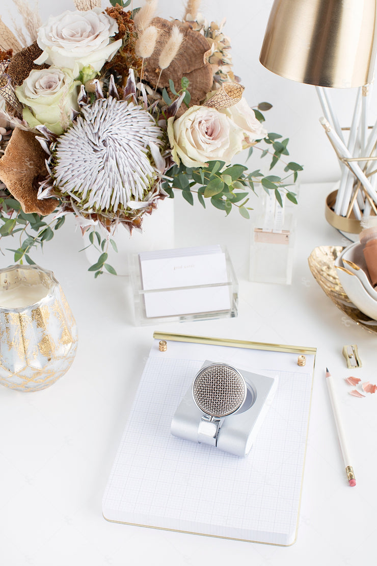 warm neutral desktop with neutral florals, blank paper, gold accents, mic, and a gold desk lamp