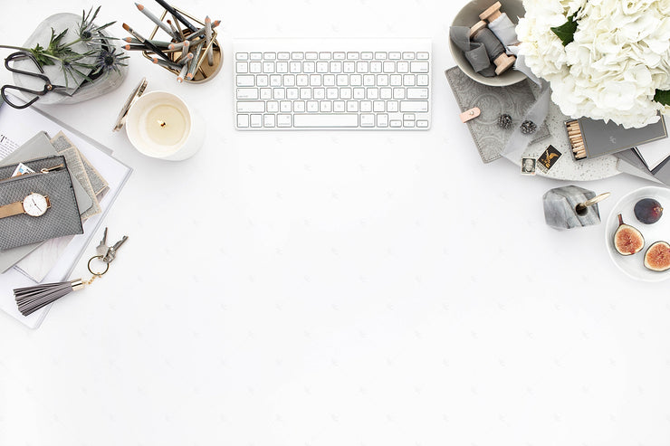 Grey desktop styled stock image with white flowers, grey accents and keyboard