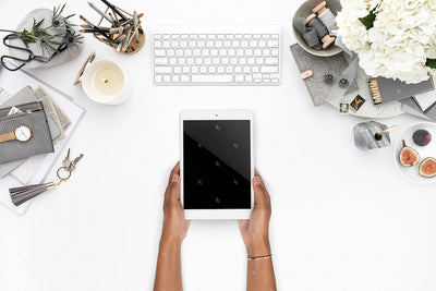 Grey desktop styled stock flatlay with hands holding an ipad