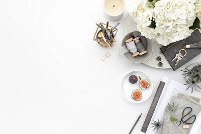 Grey desktop styled stock flatlay with white flowers, grey accents, and blank space