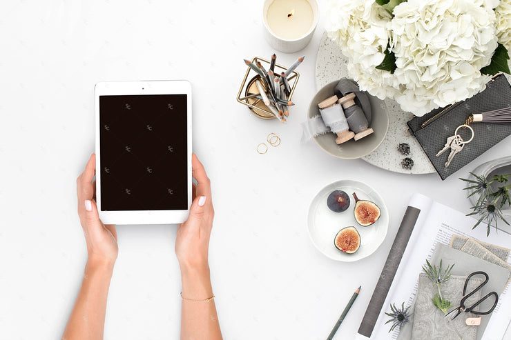Grey desktop styled stock flatlay with white flowers, grey accents, and hands holding an ipad