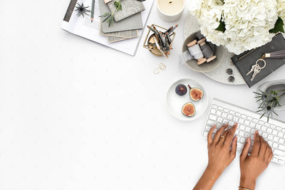 Grey desktop styled stock flatlay with white flowers, grey accents, with hands typing