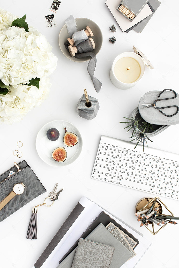 Grey desktop styled stock flatlay with white flowers, grey accents and a keyboard