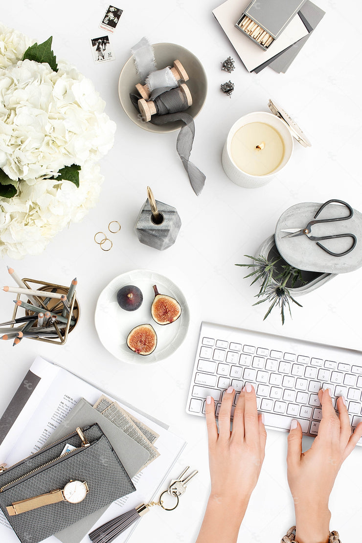 Grey desktop styled stock flatlay with white flowers, grey accents and hands typing