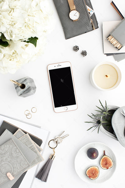 Grey desktop styled stock flatlay with white flowers, grey accents and an iphone