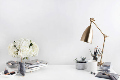 Grey desktop styled stock image with white flowers, grey accents and a gold lamp