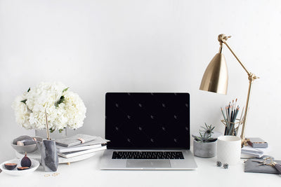 Grey desktop styled stock image with white flowers, grey accents and a laptop