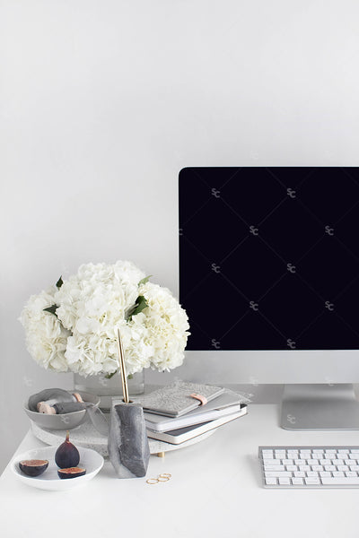 Grey desktop styled stock image with white flowers, grey accents and a desktop computer