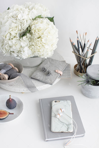 Grey desktop styled stock image with white flowers, grey accents and notebook