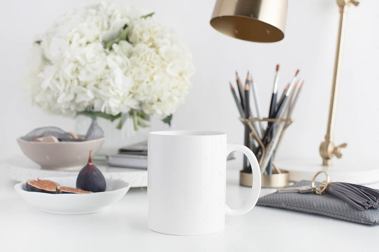 Grey desktop styled stock image with white flowers, grey accents and blank mug