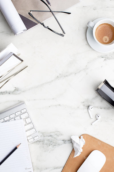 stock image of black and white desk accessories on a marble background