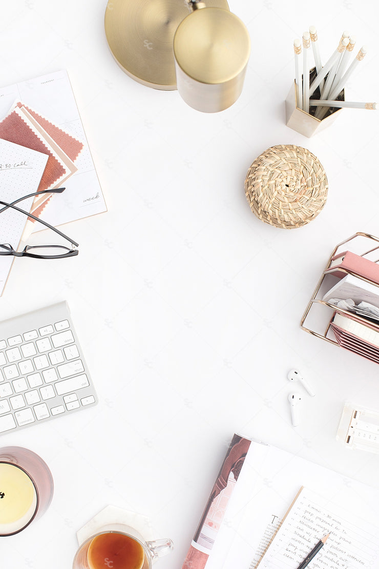 pink editorial style office desktop image with a crisp white background, dusty rose accessories