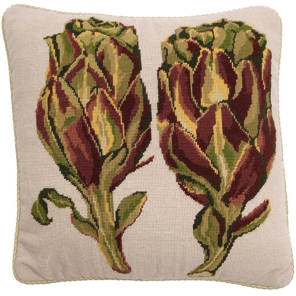 Square needlepoint cushion featuring two artichokes in green and brown on a cream background and cream piping.