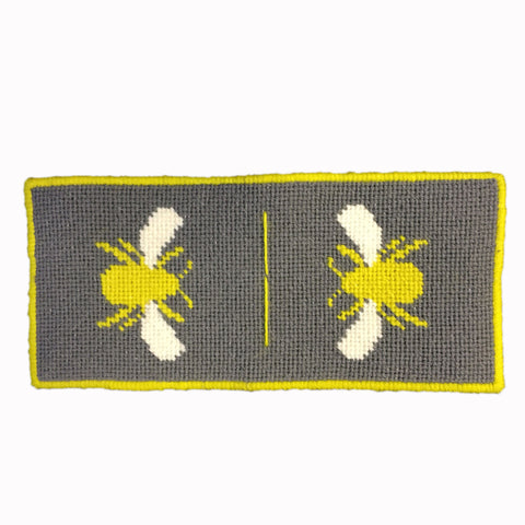 handmade needlepoint needlecase in grey with bright yellow bumble bee on either side.
