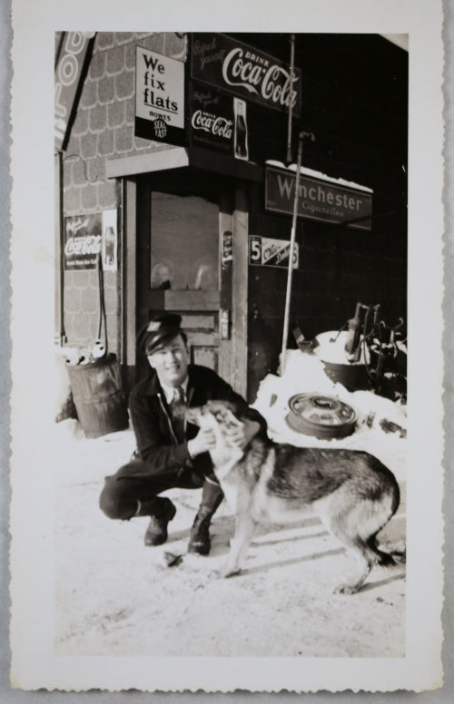 Photo of man and his dog, on front of gas station with ads ~1940s