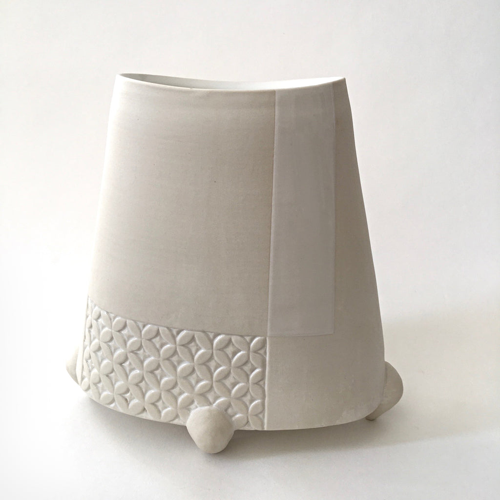 White tapered porcelain vessel with rectangular patches of carved patterns and three feet by Yoshi Fujii at Cottage Curator - Sperryville VA Art Gallery