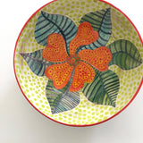 Top view of a round ceramic bowl with patterned orange and green flower and green polka dots by Sara Schneidman at Cottage Curator, Sperryville VA Art Gallery