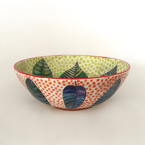 Side view of a round ceramic bowl with patterned blue and green leaves with red polka dots on the outside and green polka dots on the inside by Sara Schneidman at Cottage Curator, Sperryville VA Art Gallery