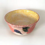 Interior view of a ceramic bowl with pink flowers on a red dotted background on the outside and yellow polka dots on the interior by Sara Schneidman at Cottage Curator - Sperryville VA Art Gallery