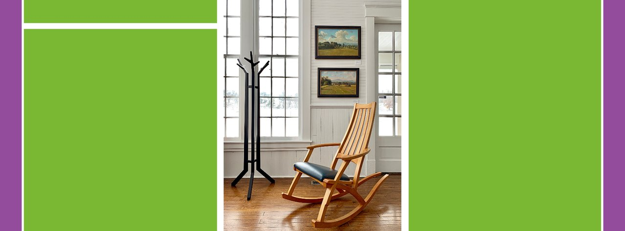 Gallery view with rocking chair, coat rack and painting
