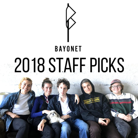 "5 people sit on a couch smiling, above them are the words ""2018 staff pics"" with the bayonet records logo"