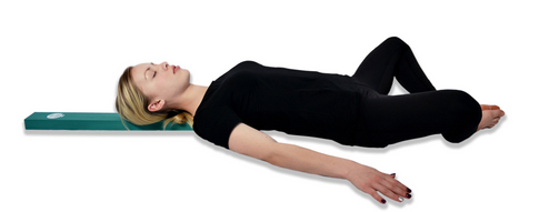 Woman lays on The Beam by Nimbleback Inc. to release back tension and improve posture and alignment.
