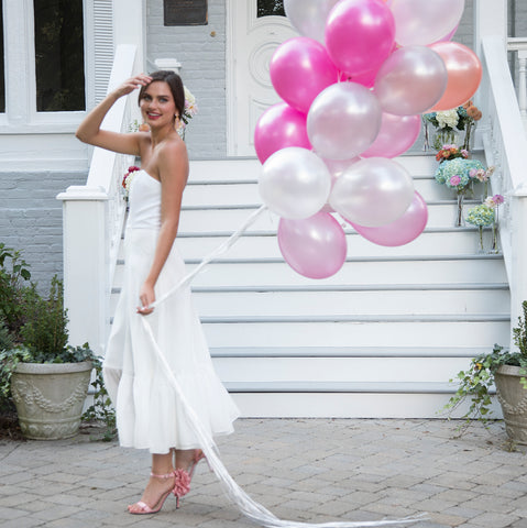 Bride wearing tea length flowy breezy white romantic strapless wedding dress to outdoor shower with balloons
