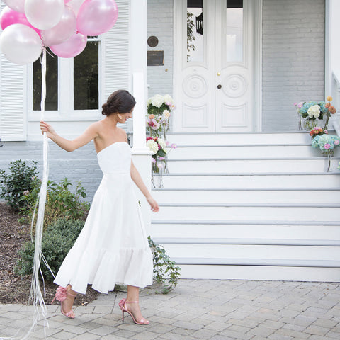 Bride walking with balloons in flowy rustic romantic ruffled tea length white strapless rehearsal dinner dress