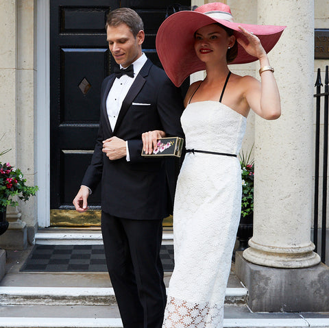 Bride wearing Jane Summers strapless white lace tea length civil ceremony wedding dress and pink hat with black feathers with groom in black tuxedo