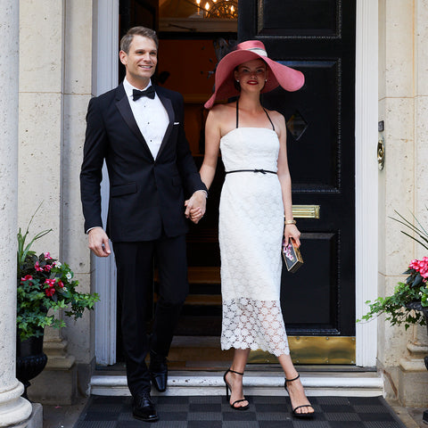 Bride wearing Jane Summers strapless white lace tea length going away dress with a pink hat with black feathers and groom wearing a black tuxedo