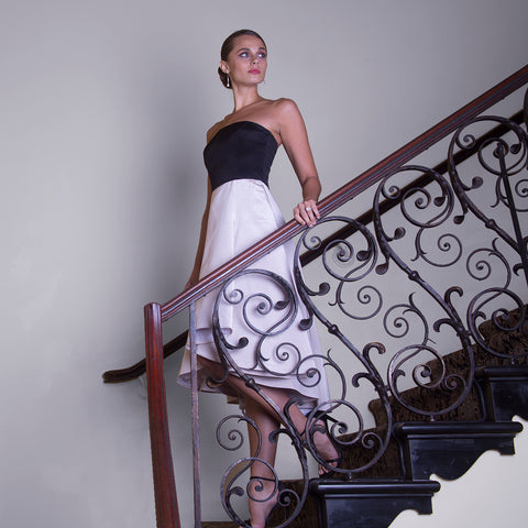 Bride walking down stairs in little black and white strapless high low hem dress to wedding reception