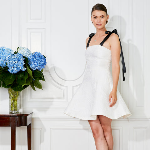 Bride wearing simple casual short white rehearsal dinner dress with black ribbon straps and blue hydrangeas