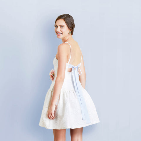 Bride wearing white floral bridal shower dress with open back and light blue ribbon tie back
