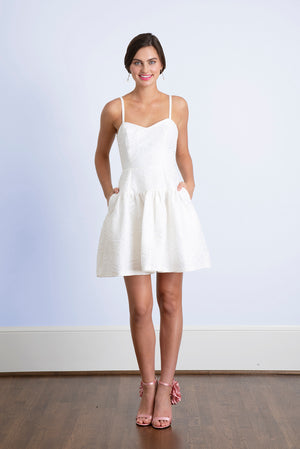 Bride with hands in pockets wearing short white dress with sweetheart neckline