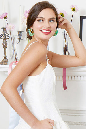 close up of bride wearing backless white bridal party dress & Bounkit earrings