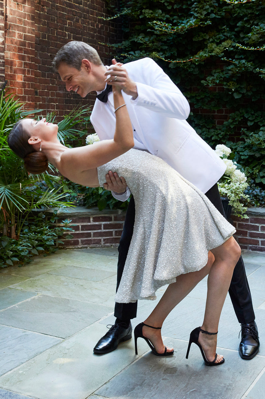 Bride twirling during first dance in sequin strapless short off white wedding reception after party dress