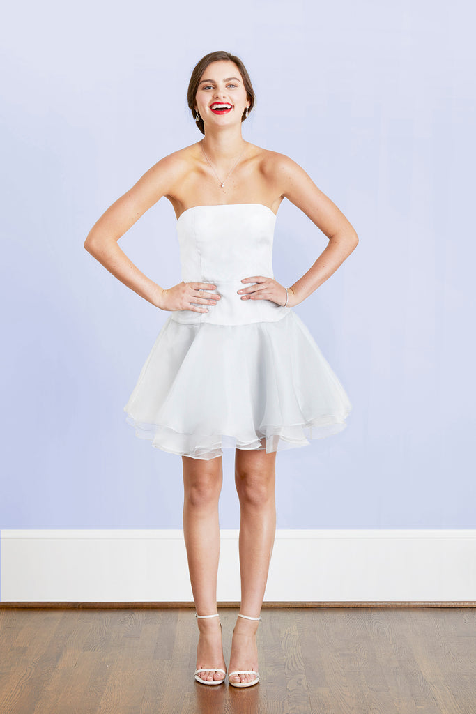 Happy stylish modern bride wearing short fun white wedding reception after party first dance dress