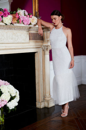 Bride wearing modern designer off white sequin tulle wedding cocktail dress with mantle and flowers
