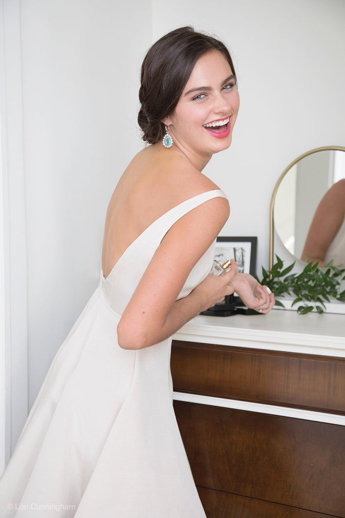 bride getting ready for rehearsal in backless off white wedding reception dress spraying perfume