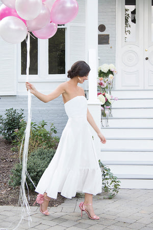 Bride wearing flirty boho chic simple white strapless tea length wedding dress to outdoor rehearsal dinner reception