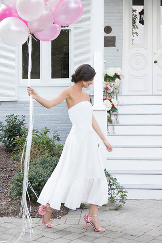 Bride wearing casual strapless white tea length wedding dress to a destination rustic romantic venue beach wedding