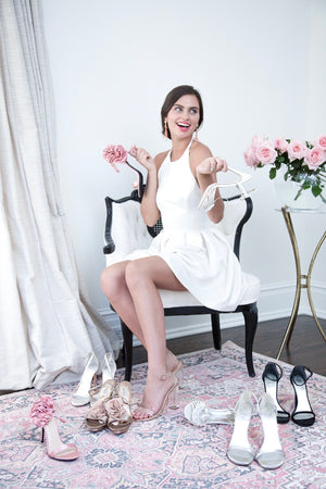 Bride-to-be in a modern white engagement photo and after party outfit deciding on wedding dress shoes