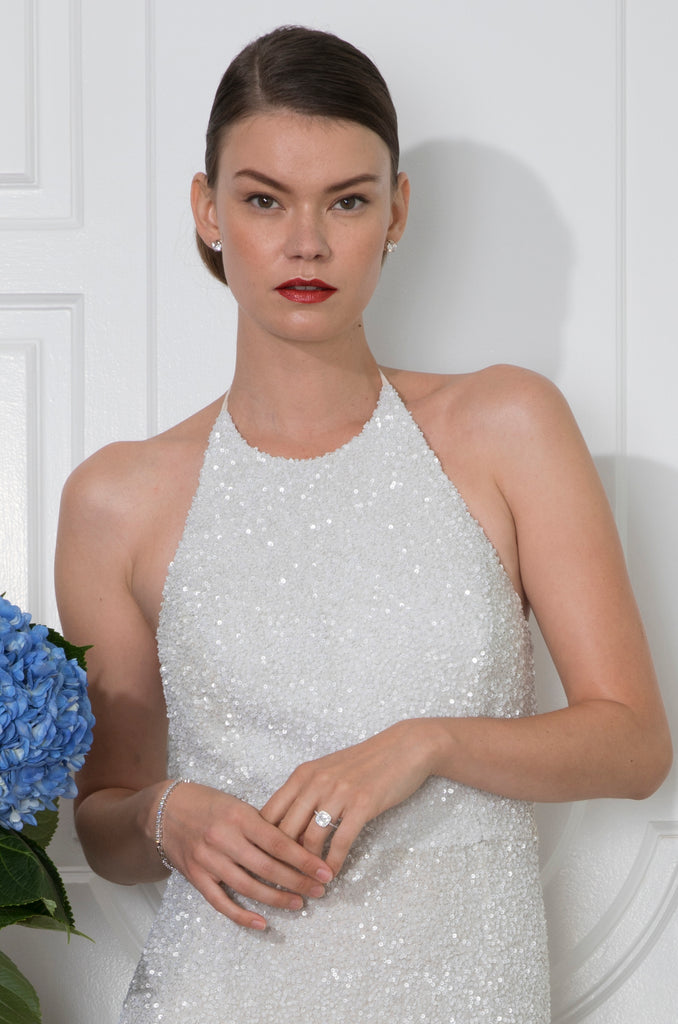 Close up of sophisticated bride with sleek bun wearing an elegant off white halter neck wedding gown