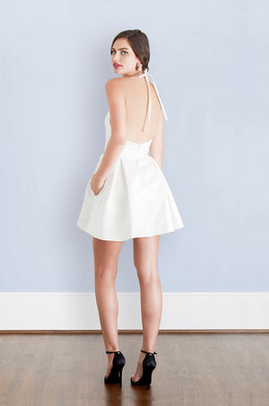 Bride wearing backless little white dress with pockets