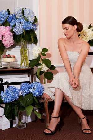 Bride wearing off white cocktail dress wedding after party dress surrounded by beautiful flowers in engagement photo