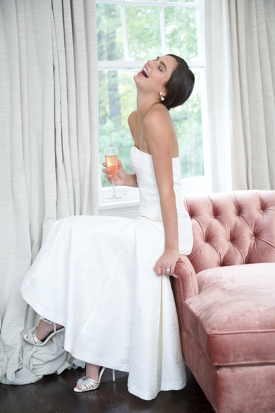 Bride wearing flattering white strapless tea length wedding dress to rustic outdoor rehearsal dinner cocktail hour reception